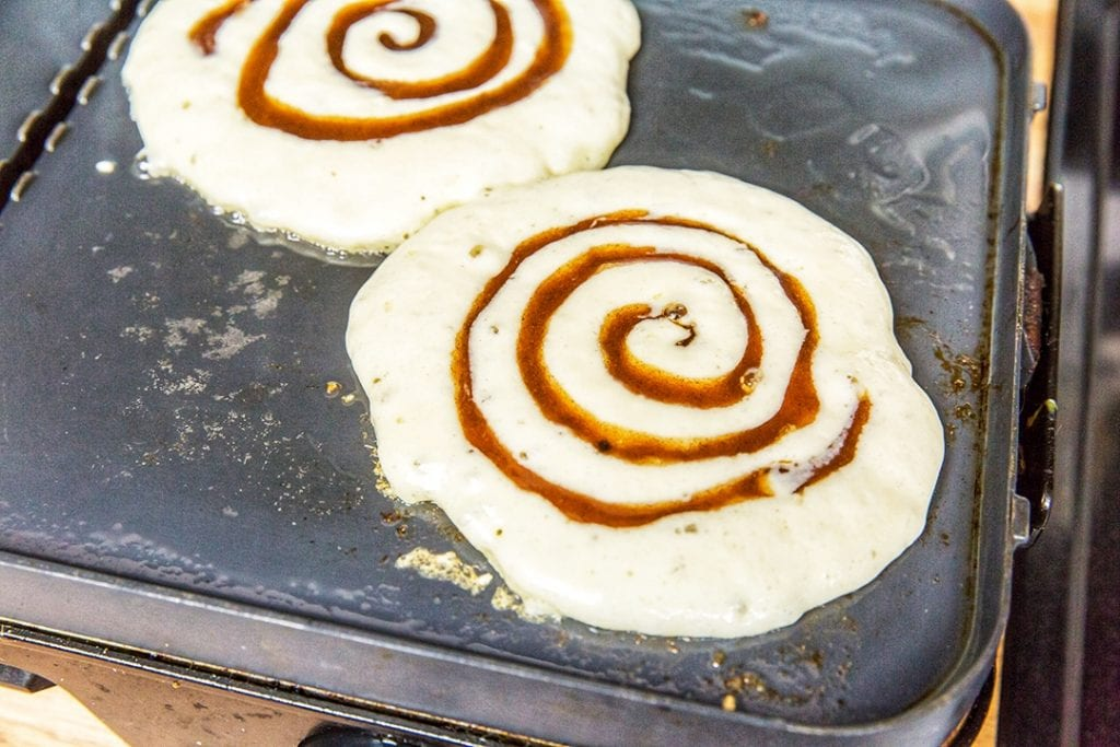 Cinnamon Roll Pancakes on Griddle