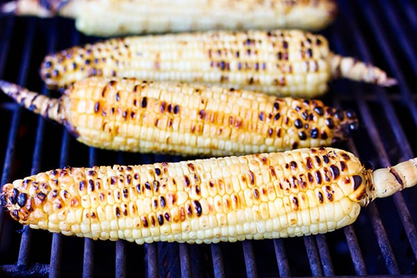 Fresh ears of corn are grilled until browned and smoky then coated in a mixture of sour cream, mayo, chili powder, and cotija cheese. Topped with fresh lime juice, this Grilled Mexican Street Corn is the perfect version of Mexican Elote!