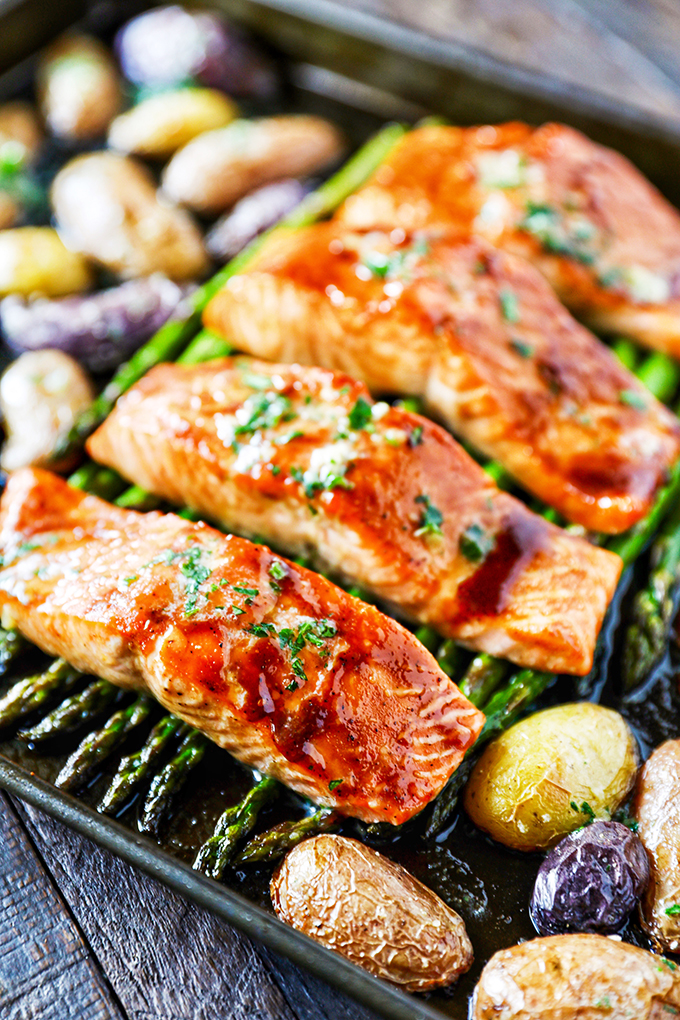 This Sheet Pan Salmon Dinner recipe is so easy to make and absolutely loaded with flavor! Glazed salmon with garlicky roasted potatoes and asparagus and everything cooks on the same pan