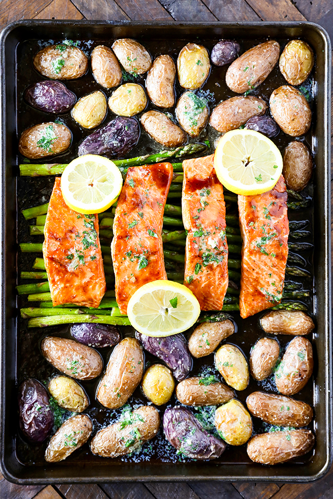 This Sheet Pan Salmon Dinner recipe is so easy to make and absolutely loaded with flavor! Glazed salmon with garlicky roasted potatoes and asparagus and everything cooks on the same pan.